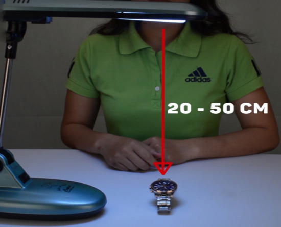 sạc đồng hồ dạ quang bằng đèn, đặt cách bóng đèn khoảng 20-50 cm trong thời gian từ 15-30 phút.